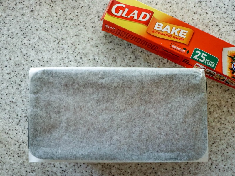 Cover tin with piece of baking paper.