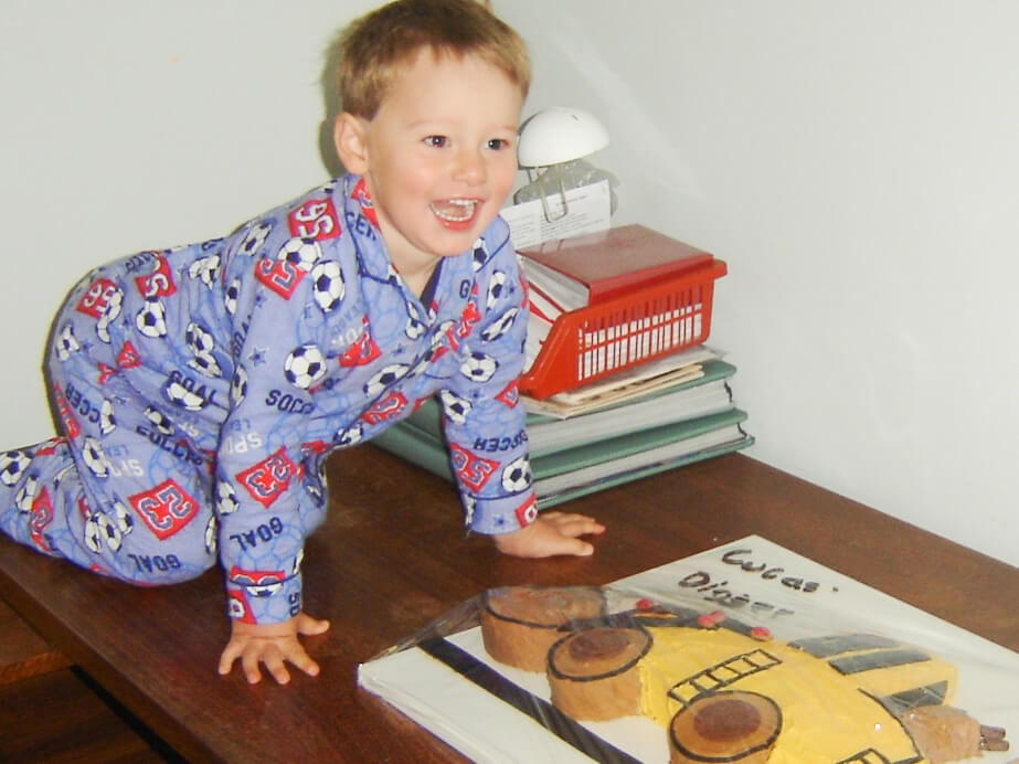 Lucas and his 3rd birthday cake, a digger. Photo source: Judith Salecich.