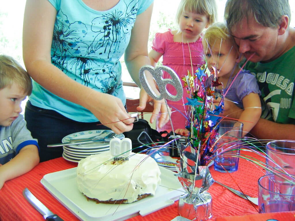 Our daughter preparing her father's 60th birthday (carrot) cake, while her husband and children look on. Photo source: Judith Salecich.