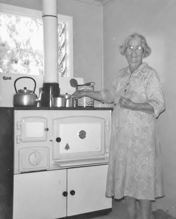 Nan, in her 80s, standing by her new combustion stove. Photo source: Beaumont Family archives.