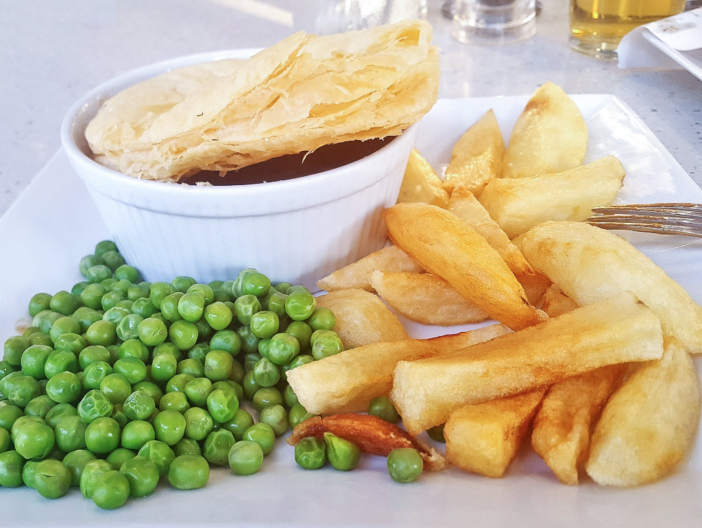 Steak and Ale Pie served with potato chips and peas. Photo source: Judith Salecich 2018.