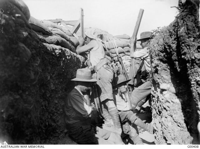 1915. In an Australian trench at Anzac showing a man using a periscope rifle, while a comrade 'spots' for him through a periscope. The periscope rifle was invented by an Australian soldier on Gallipoli. Photo source: Australian War Memorial. Public domain.