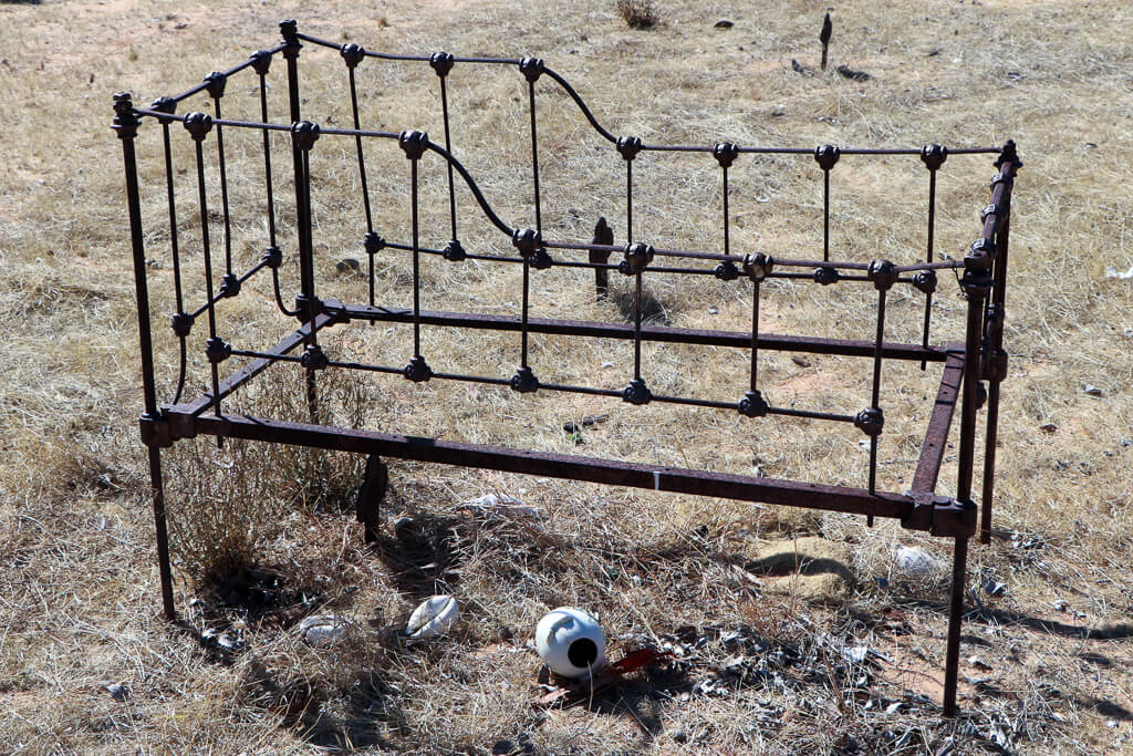 Croydon Cemetery: A child's grave marked by a rusting iron cot.